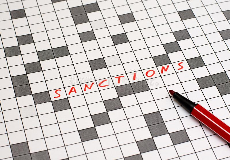 Sanctions. Text in crossword. Red letters. Close-up royalty free stock photography