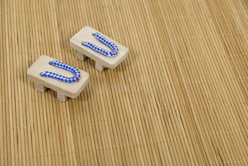 Sandálias azuis do Geta na esteira da grama fotos de stock