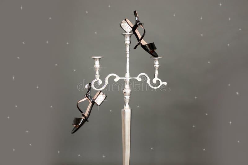 Sandálias bege pretas do vintage com os cristais de rocha que penduram de um castiçal de prata em um fundo cinzento Forma incomum fotografia de stock royalty free