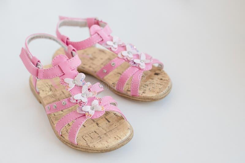 Sandálias cor-de-rosa do verão do bebê com a borboleta isolada em um fundo branco Sapatas confortáveis na moda para o verão foto de stock royalty free