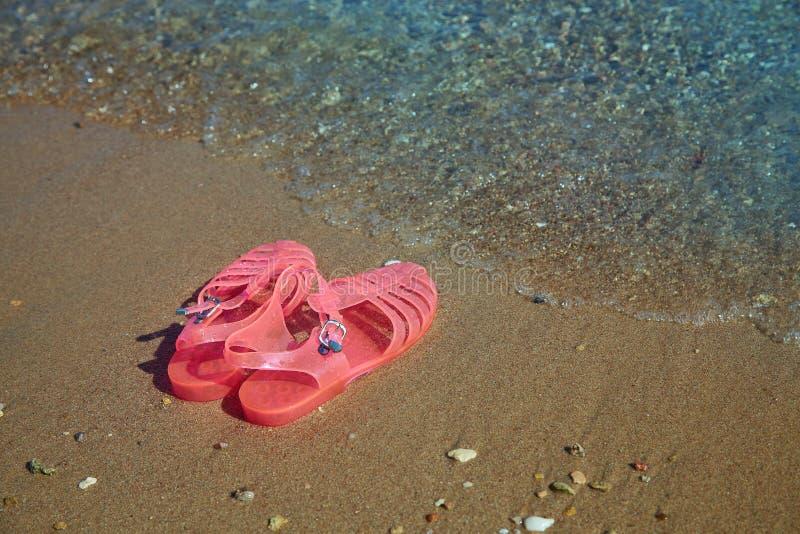 SANDÁLIAS da GELEIA das mulheres cor-de-rosa em uma costa de mar SAPATAS LISAS DA PRAIA DO VERÃO DAS GELEIAS DAS SENHORAS imagem de stock