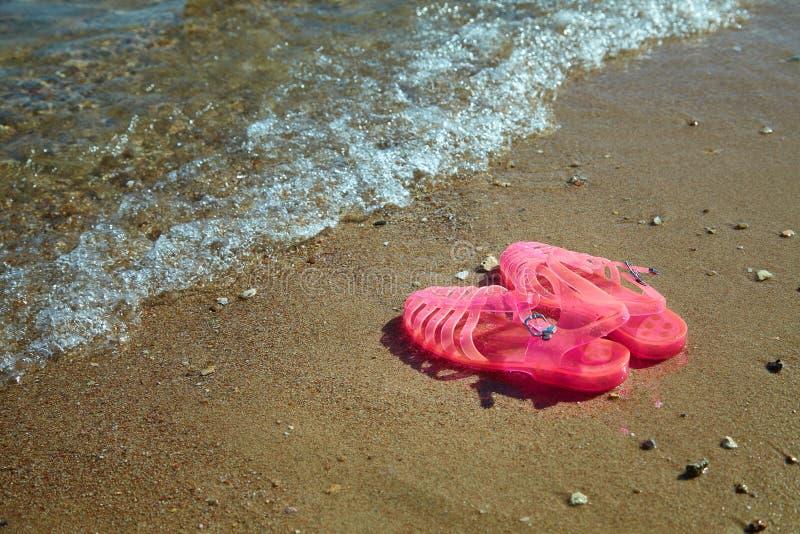 SANDÁLIAS da GELEIA das mulheres cor-de-rosa em uma costa de mar SAPATAS LISAS DA PRAIA DO VERÃO DAS GELEIAS DAS SENHORAS foto de stock royalty free