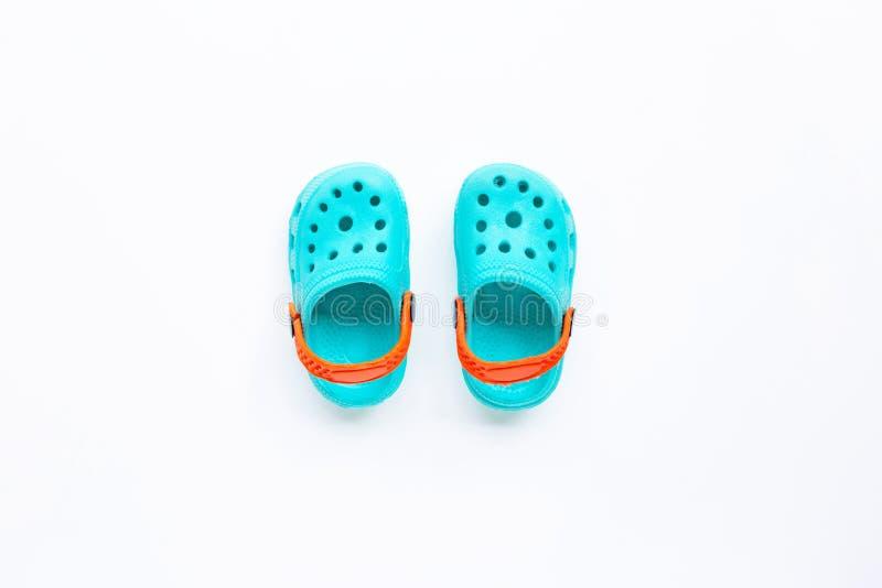 Sandálias de borracha de crianças azuis sobre fundo branco imagens de stock royalty free
