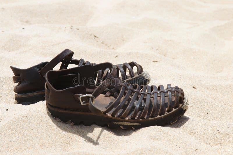 Sandálias de couro na areia fotografia de stock
