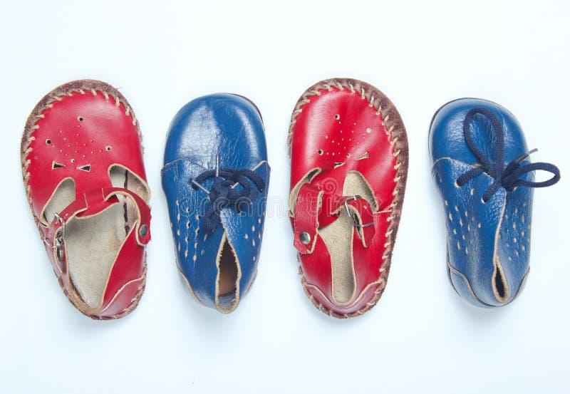 Sandálias de couro vermelhas do bebê e sapatas azuis fotografia de stock