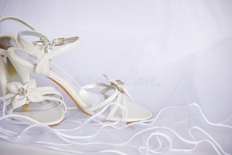 Sandálias e flores do casamento sobre o véu fotografia de stock
