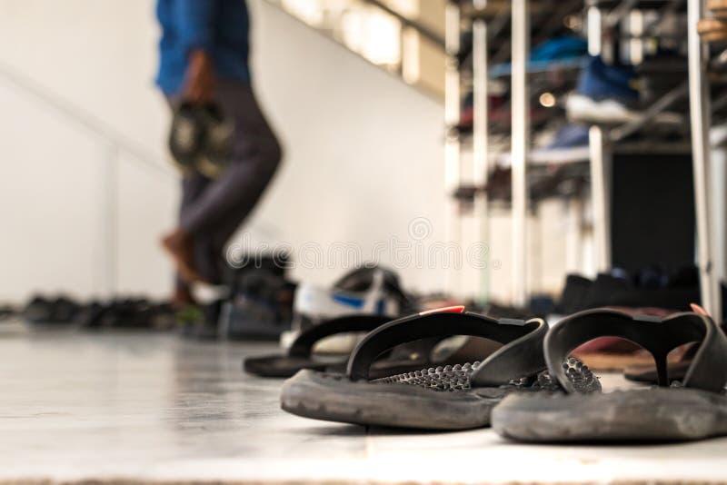 Sandálias fora da entrada principal de uma mesquita com uma oração que decola suas sapatas como o fundo do borrão no homem, Maldi fotografia de stock