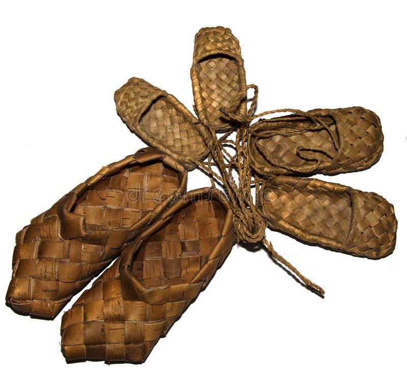 sandálias tecidas madeira do vidoeiro da sapatilha para o desgaste diário na vila em um fundo de madeira fotografia de stock