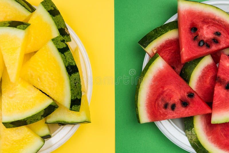 Sandía sin semillas roja y amarilla cortada en las placas, fondo en colores pastel, endecha plana imagen de archivo