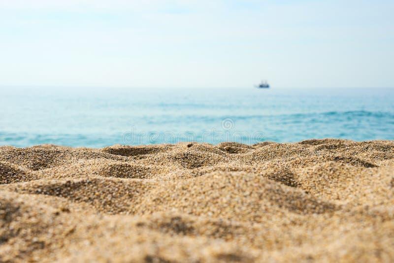 Sand auf dem Strandabschluß oben mit unscharfem Meer, Schiff und Wellen auf einem Hintergrund lizenzfreie stockfotografie
