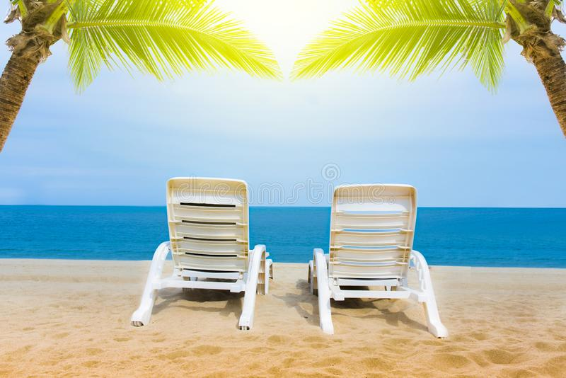Sand beach with coconut trees with two chairs and bokeh beach tropical background, summer vacation and travel ideas, relaxation stock photo