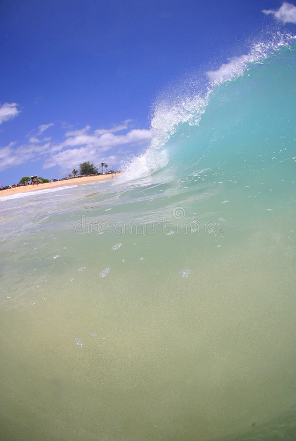 Sand Beach Wave and Blue Sky. Photo of a wave breaking on the shore at Sandy Beach on the island of Oahu in Hawaii stock photos