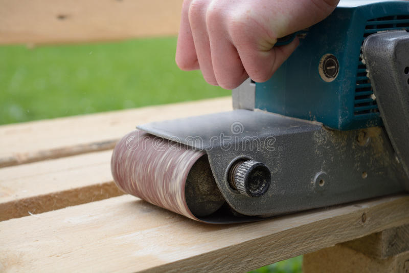 Sand with belt sanders board. Person with looped belt sanders softwood stock images