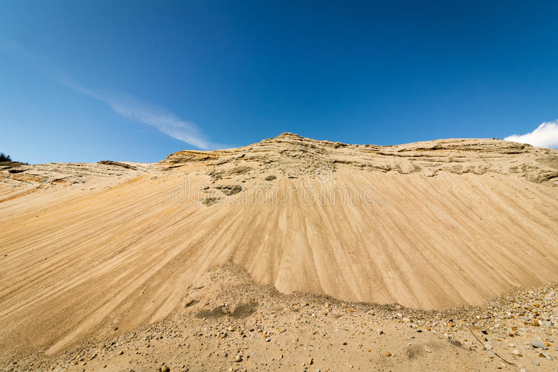 Sand in a big sand pit, with blue sky and white clouds in the background, hill looks like a mountain stock image