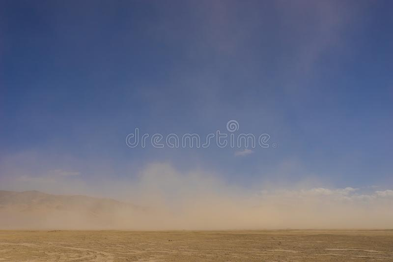 Sand Blows over Flat Desert. Wind whips sand across the flat Mojave desert in the dry climate of southern California stock photos