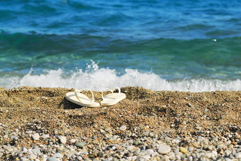 Sand, blue sea and white slippers. Focus on slippers stock photo
