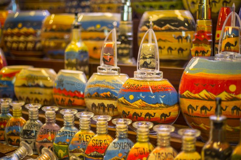 Sand bottle souvenirs at the Madinat Jumeirah Souk, Dubai, UAE. Decorative glass bottles with colored sand inside making shapes of desert and camels stock photography