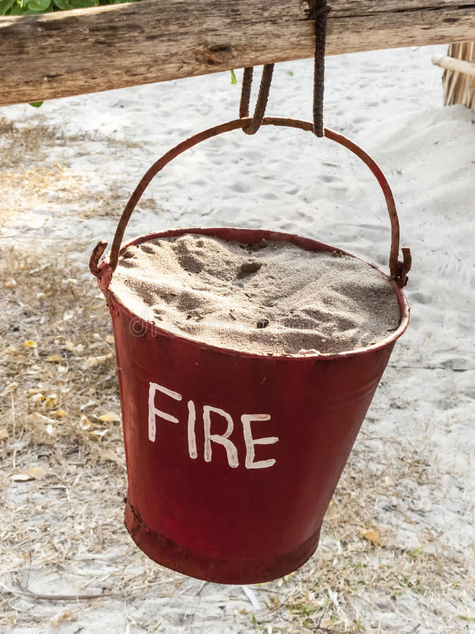 Sand bucket painted in red with fire sign and sand to extinguish stock image