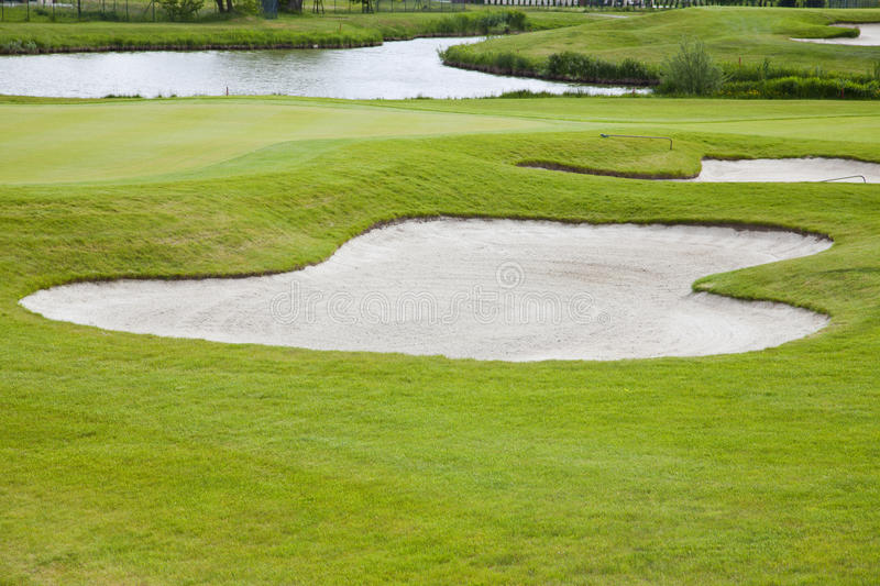 Sand bunkers on the golf course. Sand bunkers on the golf course, green field stock image