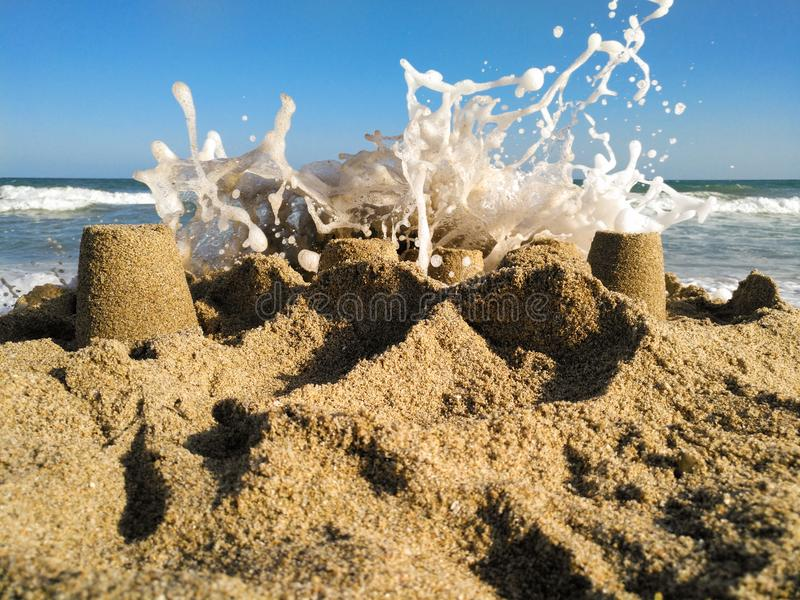 Sand castle attacked by the waves royalty free stock photos