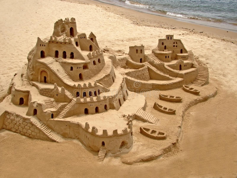 Sand castle on the beach stock images