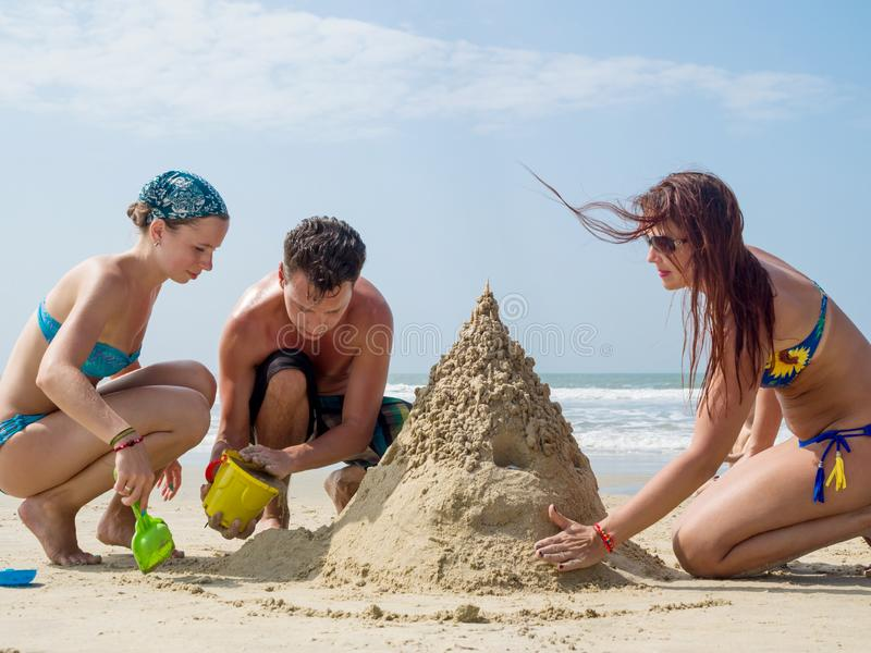 Sand castle on the beach and cheerful company of girls and a guy. A company of young people in bathing suits are building a sand castle on the shores of the royalty free stock image
