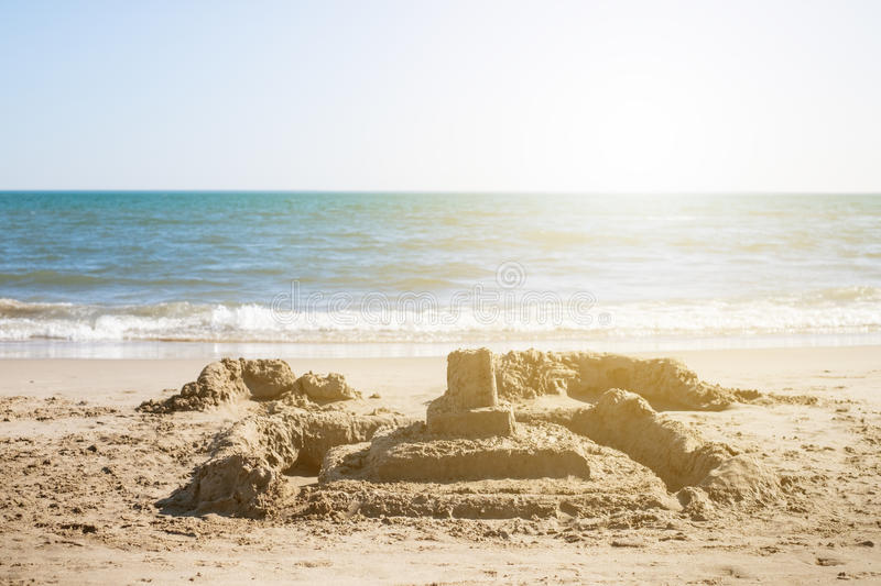 Sand castle on beach. Summer and holiday time. Relax. Sun is shining above the sea level. royalty free stock photo