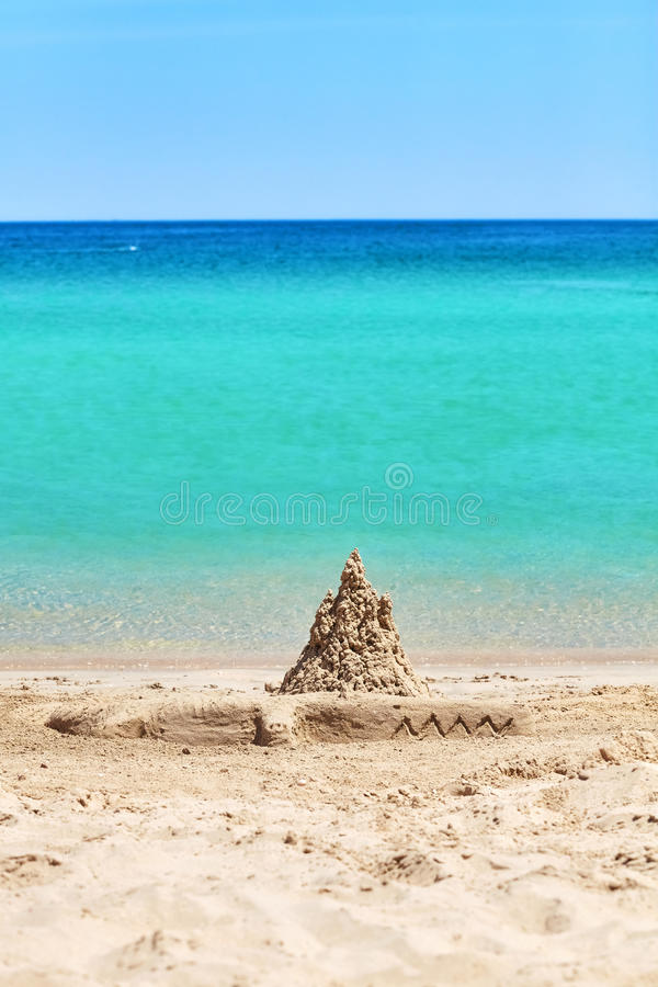 Sand castle and crocodile sculpture on beach, summer holiday con stock image