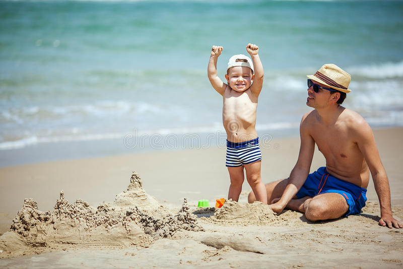 Sand castle. Father and son build sand castle stock photo