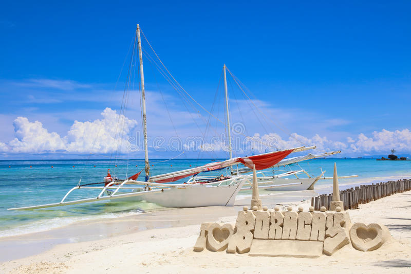 Sand castle and a sail boat on White Beach, Boracay Island, Philippines royalty free stock image