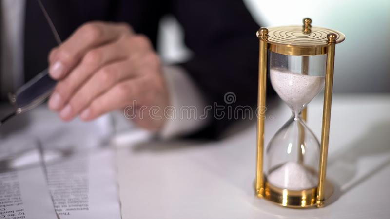 Sand clock flowing near businessman who signs important contract, time is money. Stock footage royalty free stock photo