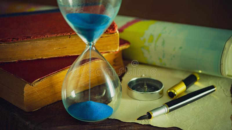 Sand clock with old books and pen with paper map on the wooden table. stock photos