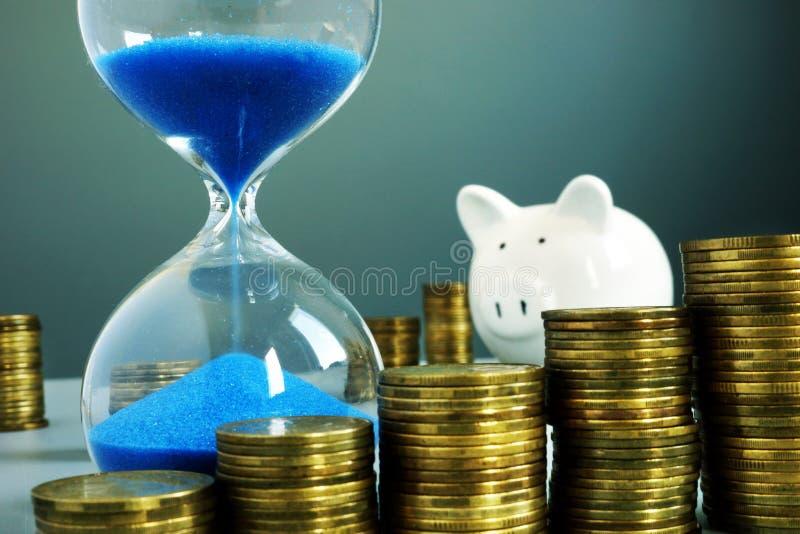 Sand clock, piggy bank and money. Bank deposit and savings. Concept royalty free stock photos