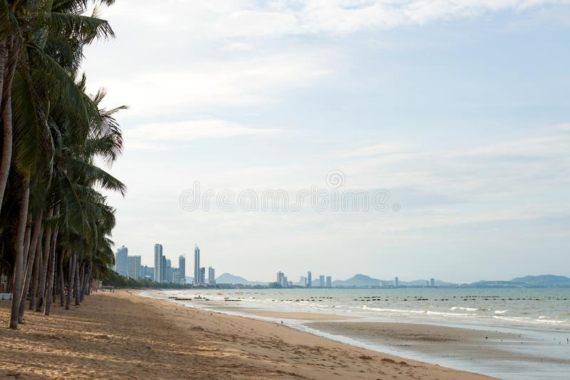 Sand coastline of long beach with palm trees. Tropical city. stock photos