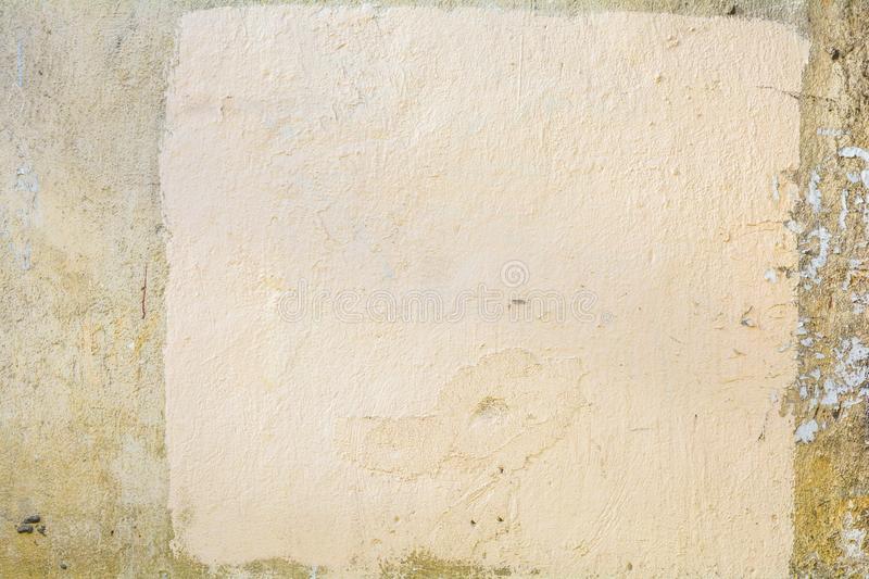 Sand color concrete wall with cracks and painted white square royalty free stock photo