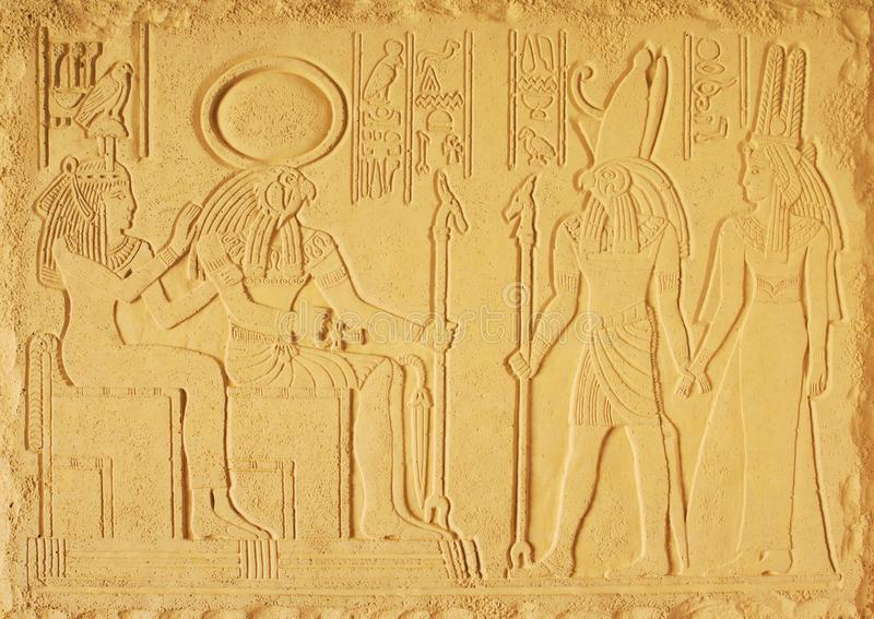 Sand color plaster bas-relief with the gods of Ancient Egypt, the sun God RA, the God Horus and the two goddesses stock images