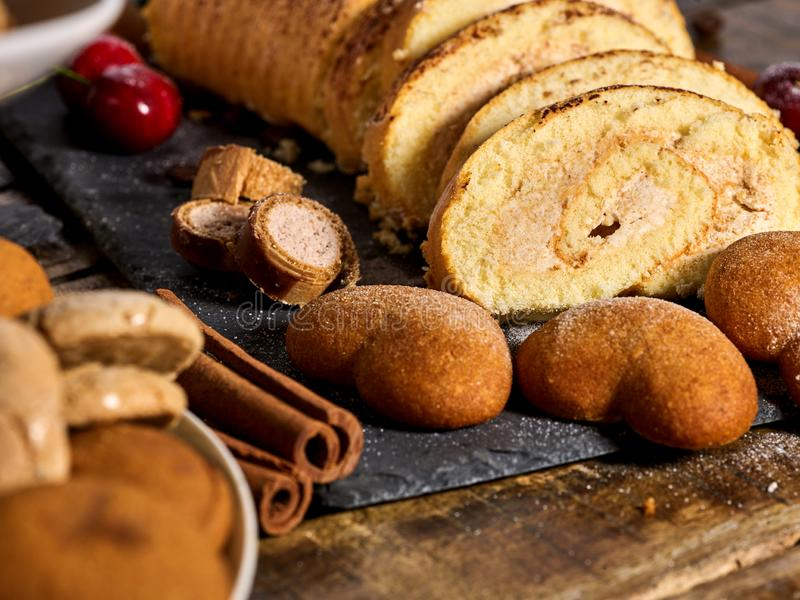 Sand cookies heart shape, rolled cake with cherry, cinnamon stick royalty free stock photo