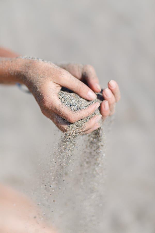 Sand in den Händen stockbild