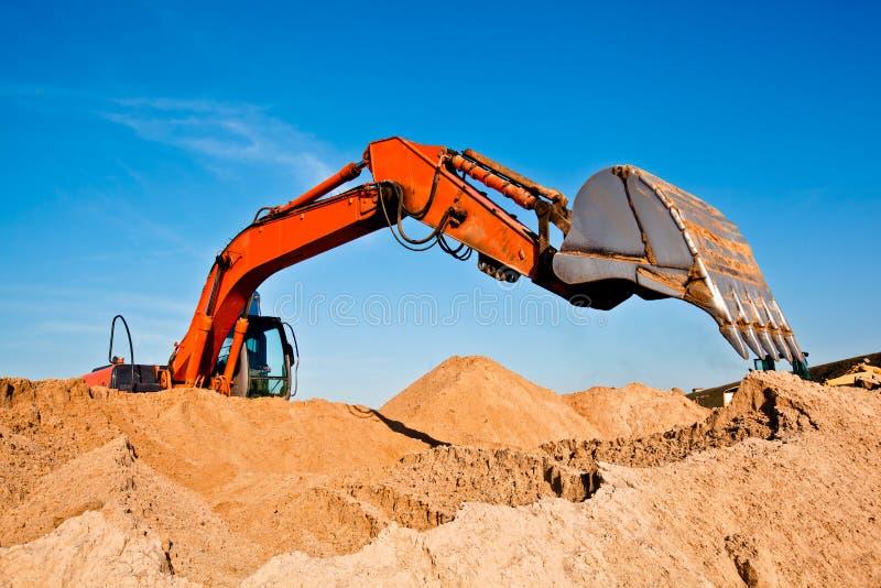 Sand, der Exkavator abbauend gräbt stockfotografie