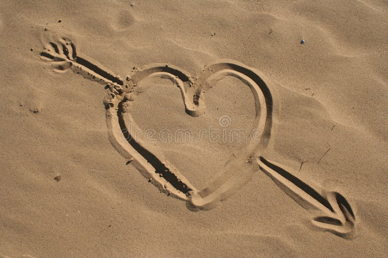 Sand drawn heart and arrow stock images