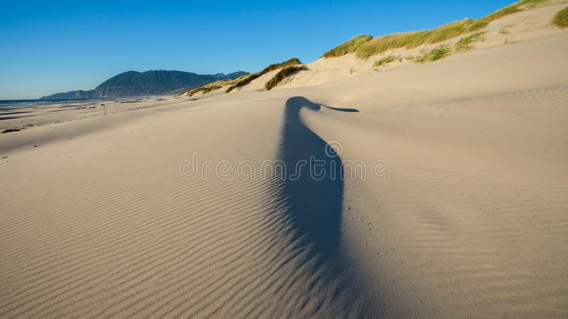 A sand dune on a beach with the sand being blown around by the wind stock images