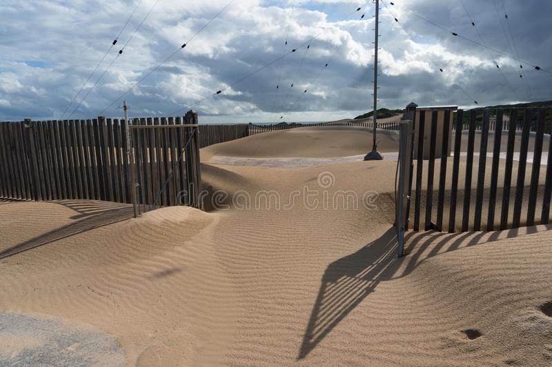Sand dune invading the landLand desertification environmental issues. Sand dune invading the land. Desertification due to climate change and overexploration stock photos
