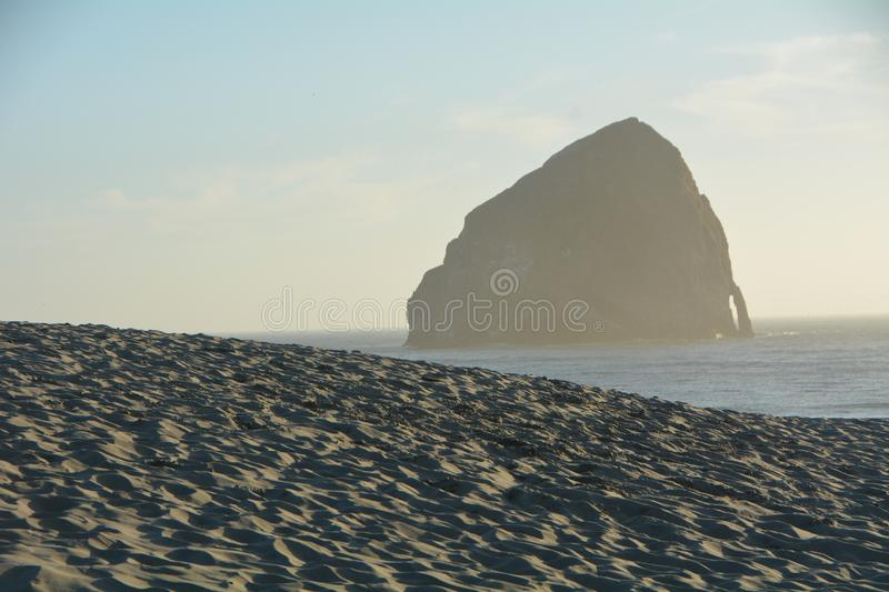 Haystack Rock and sand dune at Pacific City, Oregon stock images