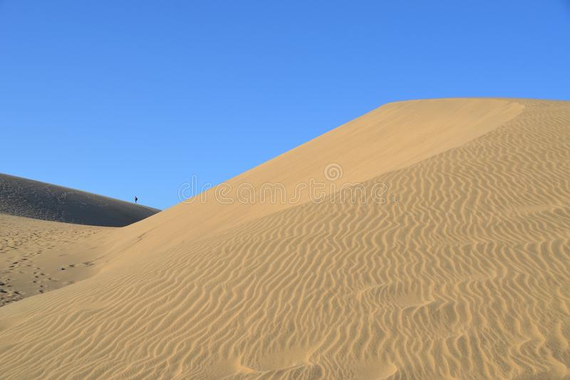 A silhouette of a man in the distance on sand dune landscape royalty free stock images