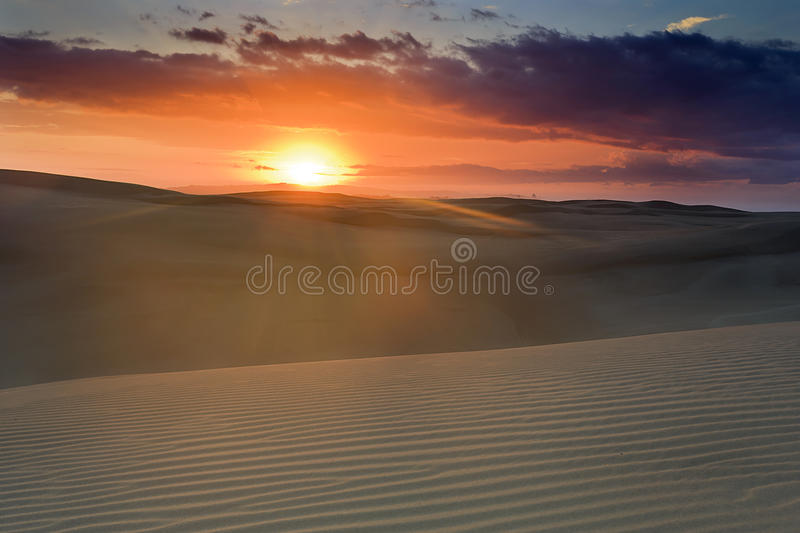 Sand Dune Sun Pink Over. Bright rising sun over land horizon in sand dunes of Stockton beach, NSW, Australia. Striped structure of soft sand hills under gentle royalty free stock photography