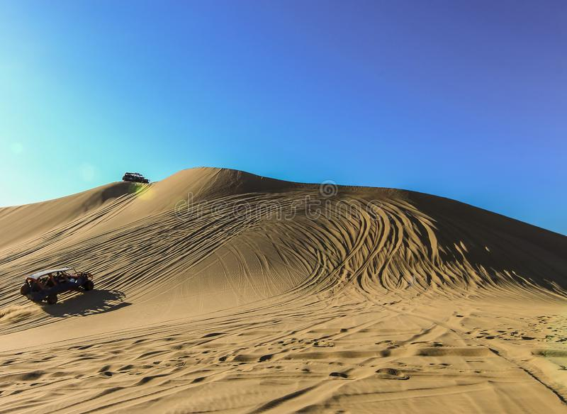 Sand dunes and buggies against blue sky at Huacachina, Peru stock photography