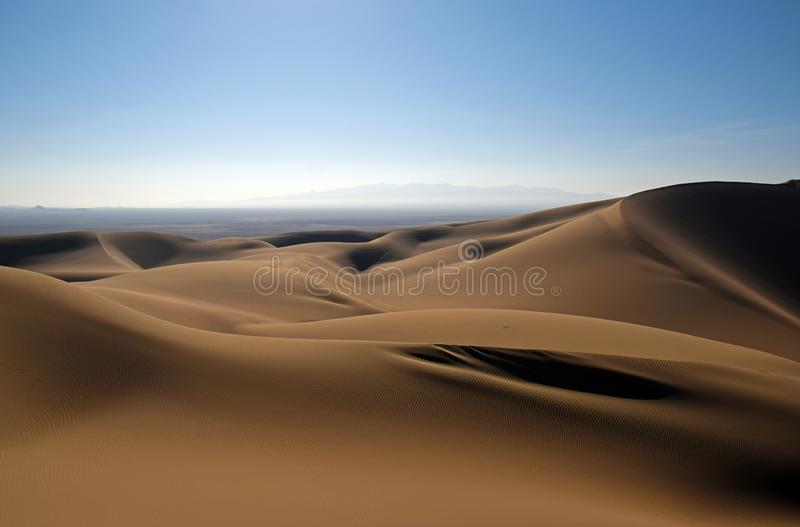 Shadows of sand dunes in desert Iran. The sand dunes in central desert of Iran with shadows and smooth shapes stock image