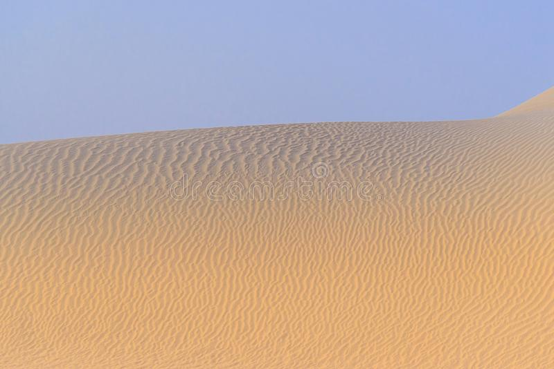 Sand dunes in the desert. Purple sky, yellow sand with small waves royalty free stock image