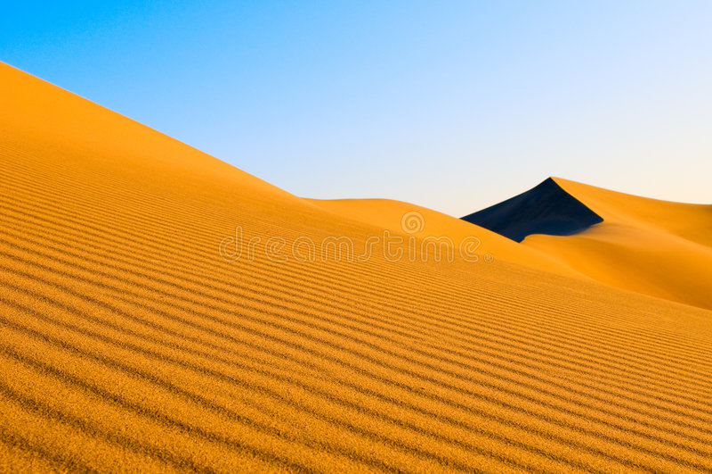 Download Sand dunes over blue sky stock image. Image of barren - 5542081