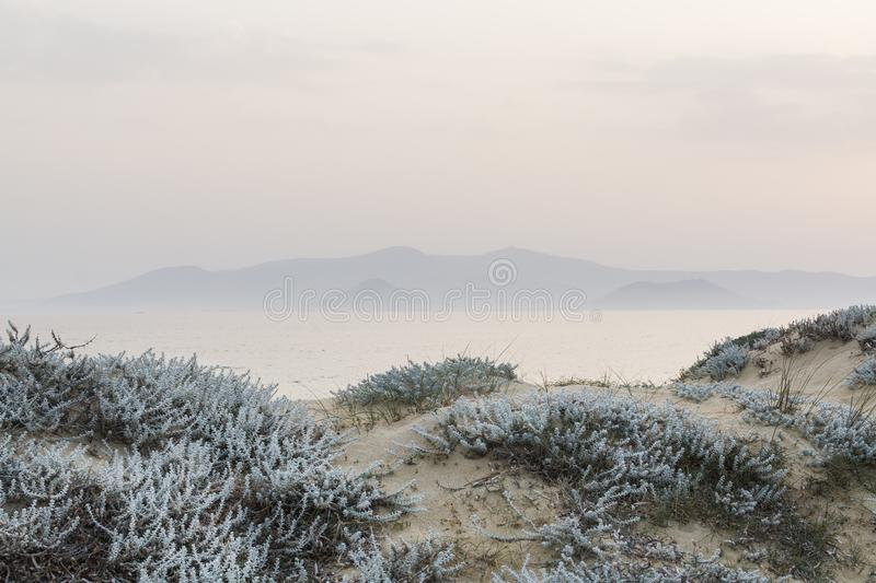 Sand dunes with sea and mountains on the background in Milos island, Greece. Shot taken at sunset, tonal perspective stock photography